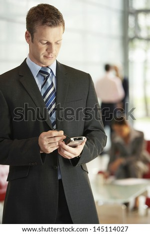 Young businessman using cellphone with stylus in office while colleagues working in background - stock photo