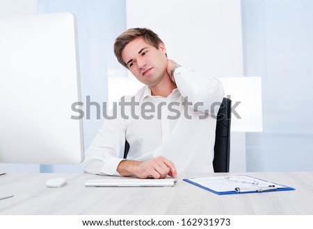 Young Businessman Using Computer Suffering From Neck Ache - stock photo