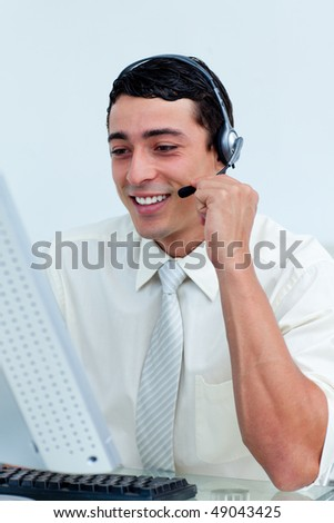Young businessman using headset working at a computer - stock photo
