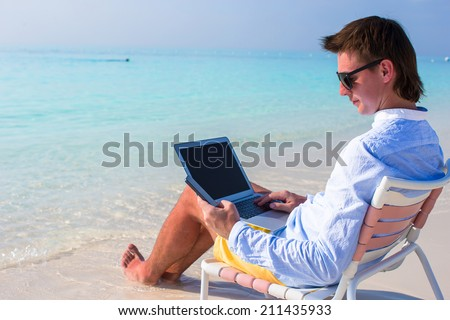 Young businessman using laptop and telephone on tropical beach - stock photo