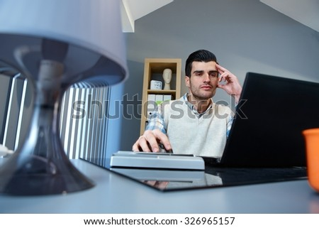 Young businessman using laptop computer at home, sitting at desk. - stock photo