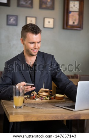 Young businessman using laptop while having food in restaurant - stock photo
