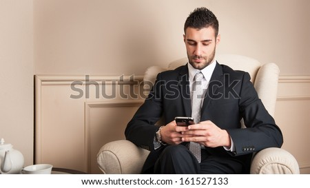 Young businessman using mobile phone sit on armchair.  - stock photo
