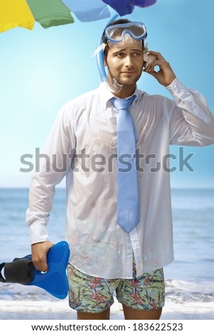 Young businessman using seashell as mobilephone on the beach wearing shirt and tie and scuba diving equipments. - stock photo