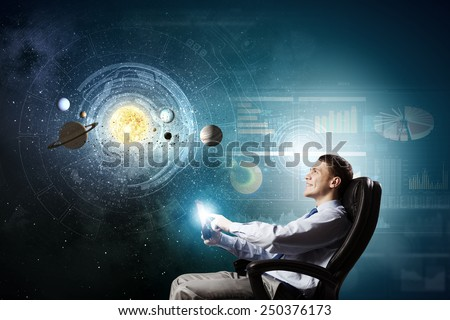 Young businessman using smart phone and planets of space spinning around - stock photo