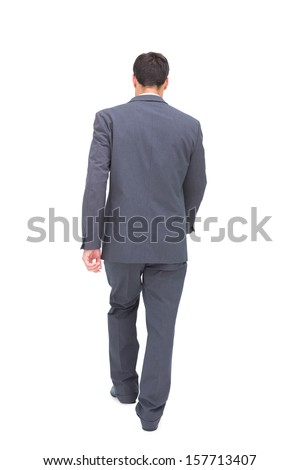 Young businessman walking away from camera on white background - stock photo