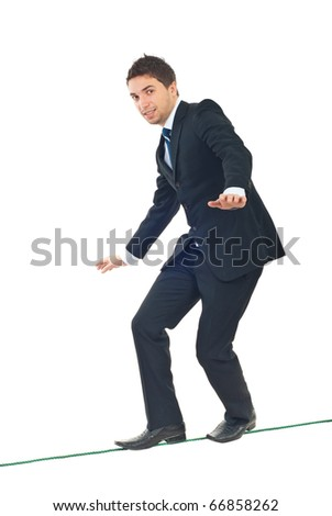 Young businessman walking on tightrope and trying to keep his balance isolated on white background - stock photo