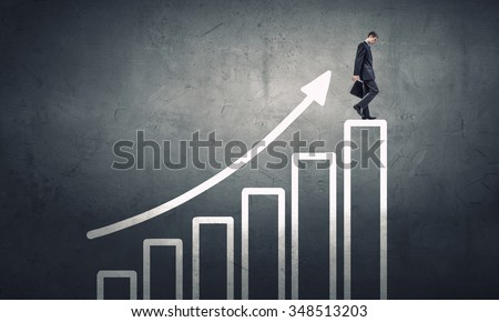 Young businessman walking up on growing graph representing success concept - stock photo