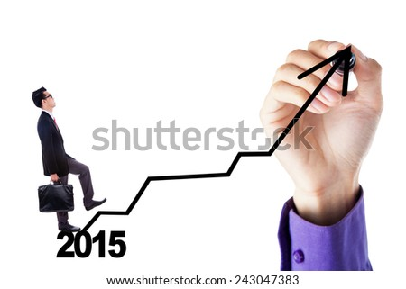 Young businessman walking upward on a business graph with number 2015 - stock photo