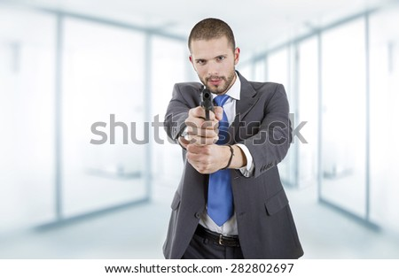 young businessman with a gun, at the office - stock photo