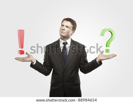 Young  businessman with a question and exclamation mark on his hand.Man makes a choice. On a gray background - stock photo