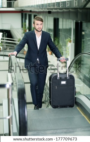 Young businessman with a suitcase and plane tickets at the airport to travel trips - stock photo