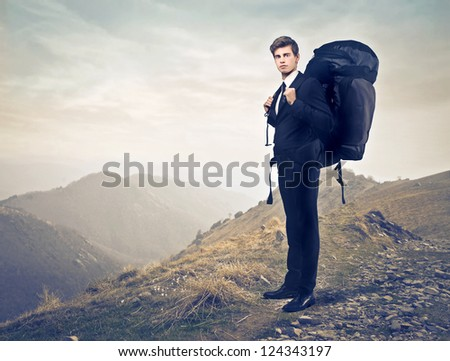 Young businessman with a travel backpack on a mountain - stock photo