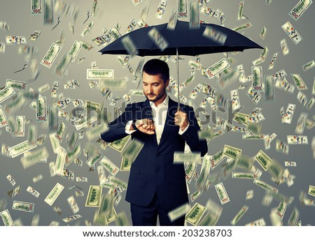 young businessman with black umbrella standing under money rain and looking at watch - stock photo