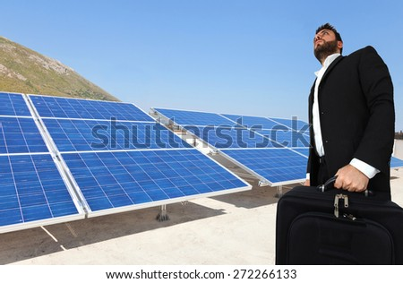 Young businessman with briefcase over big solar panels. - stock photo