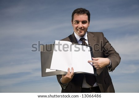 young businessman with corporate binder pointing to blank paper - outdoor environment - stock photo