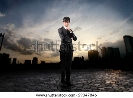 Young businessman with doubtful expression and cityscape on the background - stock photo