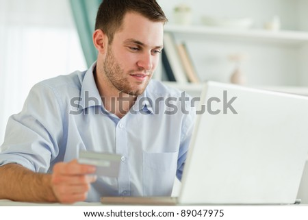 Young businessman with laptop and credit card - stock photo