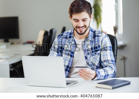 Young businessman with laptop and credit card shopping online in office. - stock photo