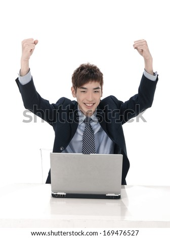Young businessman with laptop and raising his arm - stock photo