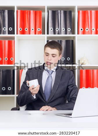 young businessman with laptop in his office - stock photo