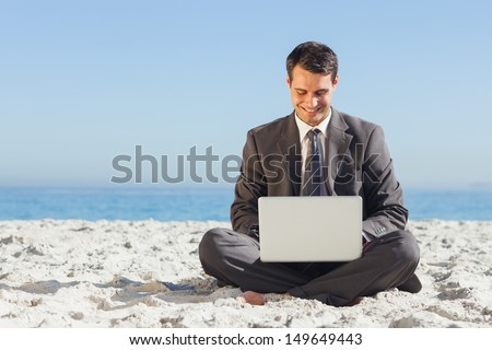 Young businessman with legs crossed typing on his laptop on the beach - stock photo