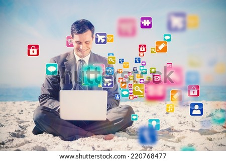 Young businessman with legs crossed typing on his laptop with colourful computer applications - stock photo