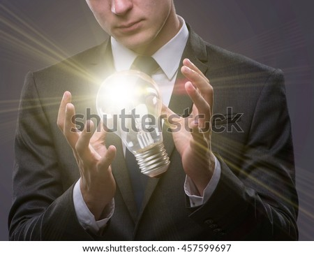 Young businessman with light bulb in idea concept - stock photo