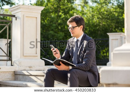 Young businessman with notepad in hand using smart phone outside on concrete columns and trees background - stock photo