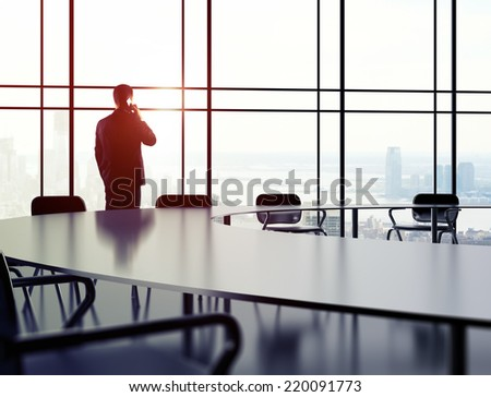 young businessman with phone standing in office - stock photo