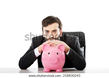 Young businessman with piggybank by a desk. - stock photo