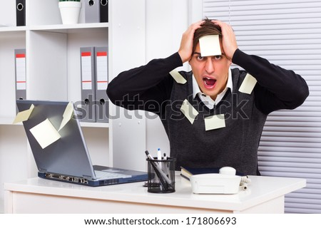 Young businessman with too much work to do,Overworked - stock photo