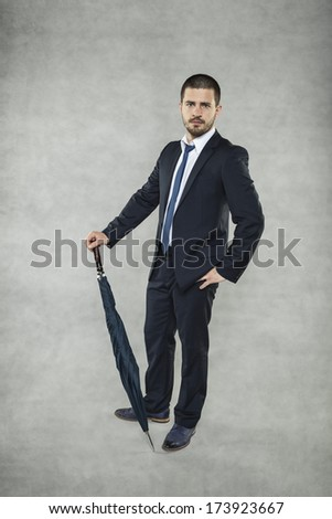 Young businessman with umbrella - stock photo