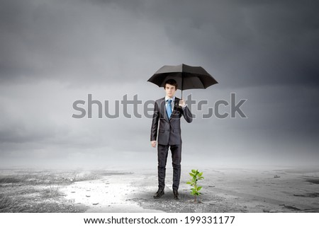 Young businessman with umbrella protecting sprout growing in desert - stock photo