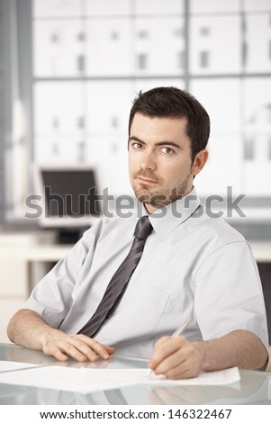 Young businessman working in bright office, sitting at desk, writing notes. - stock photo