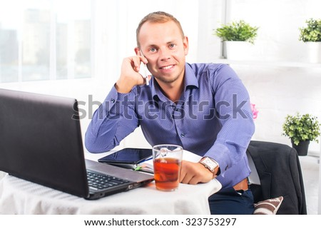Young businessman working in office, sitting at a table, looking straight and talking on the phone - stock photo
