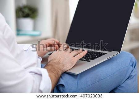 Young businessman working in office, sitting at desk - stock photo