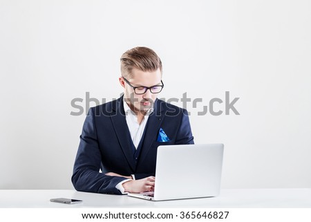 Young businessman working in office, sitting at desk, looking at laptop computer - stock photo