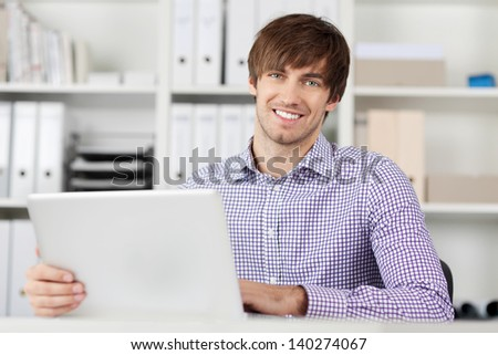 Young businessman working in office, using laptop - stock photo