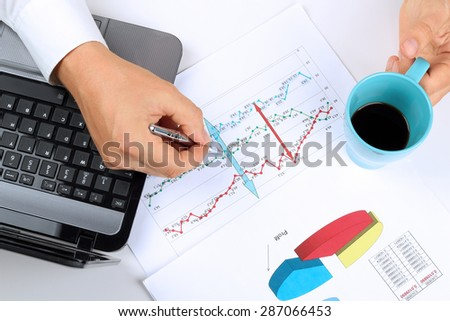 young businessman working in the office,  sitting at his desk, analyzing  data in  graphics - stock photo
