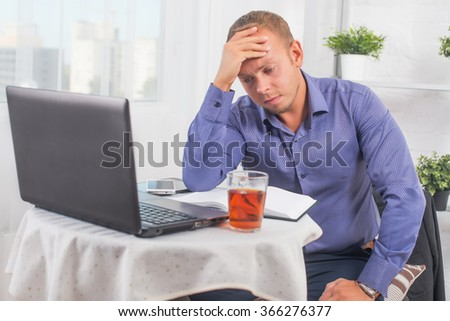 Young businessman working in the office, very concerned, solves problem, and leaned head on his hand - stock photo
