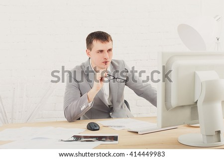 Young businessman working in white modern office interior, thoughtful, sitting at computer table. Office worker with eye glasses, job in internet. High key, soft tone. Business man in modern office.  - stock photo