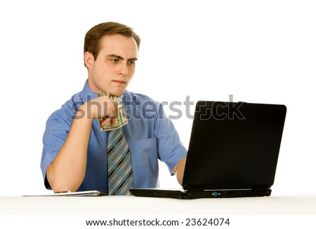 Young businessman working on a laptop holding money. Isolated on white. - stock photo
