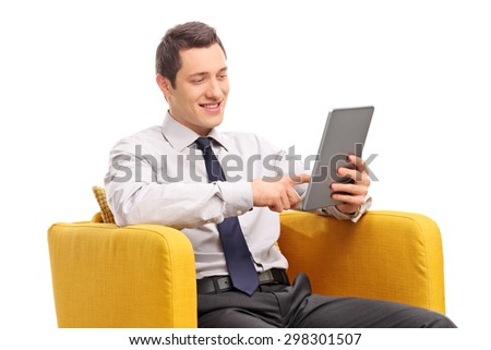 Young businessman working on a tablet seated in a yellow armchair isolated on white background - stock photo