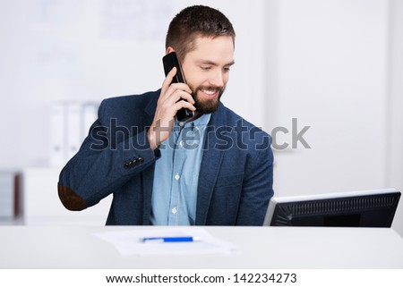 Young businessman working on computer while using mobile phone at desk in office - stock photo