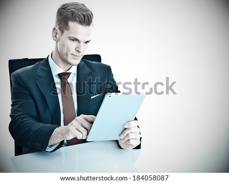 Young businessman working on his modern tablet computer / touchpad - much copyspace for own text - stock photo