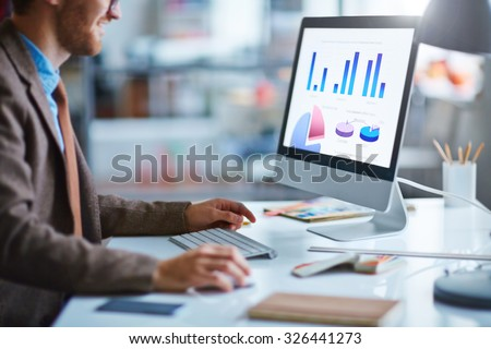 Young businessman working with electronic document in computer - stock photo