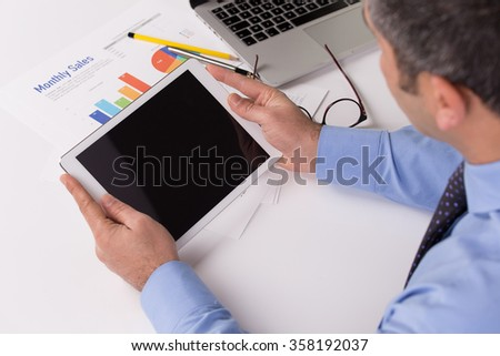 Young businessman working with modern devices, digital tablet and computer - stock photo