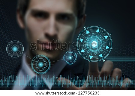 Young businessman working with modern virtual technology pressing keys on touch screen on black background - stock photo