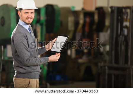 Young businessman working with tablet in factory. - stock photo